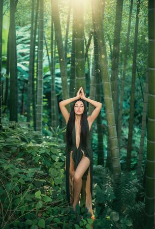 Forest nymph enjoy nature hands over head closed eyes, long legs, loose black hair sexy dress . backdrop bamboo forest fern botanical garden grove summer. spring art fantasy. artistic Georgia holiday