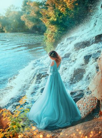 elf girl turned away open back standing on shore lake. stone splash water. Golden summer autumn. Red Hair collected decorated flowers. blue turquoise evening long lush dress. graduation party ball art