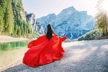 Happy cute lady tourist hair run walk rear view. Art luxury long vintage red design dress satin silk train floating fly vawy wind. Travel vacation bright sunny day divine magic Italy light sun nature