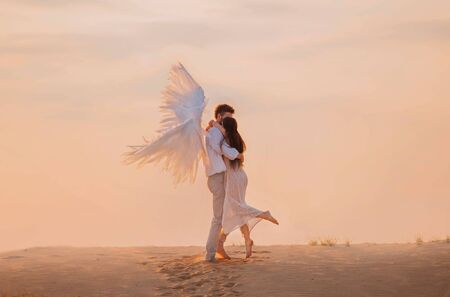 Girl and angel hugging. Brunette man in white suit with creative wings. Princess long flowing hair delicate pink elegant dress. Backdrop vanilla sky clouds, footprints in sand natural fairytale desert
