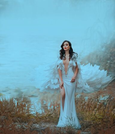 Woman with curly hair loose, in long dress leg standing on lake. Princess in white bird feather cloak fly in wind. Backdrop autumn orange grass, water surface river, blurred silhouette tree Reklamní fotografie