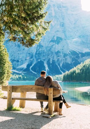 Family sits wooden bench near green tree shore of alpine Lake Braies turned away enjoys amazing beauty mountains. Woman long flowing hair bowed head to mans shoulder. Backdrop blue mountain forest