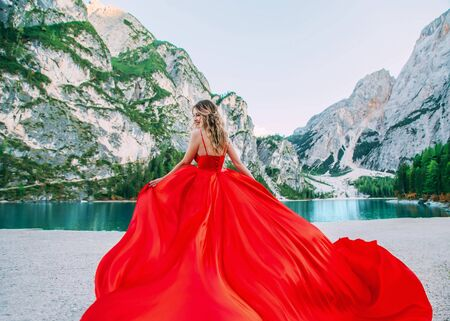 cute happy blond girl in long luxury vintage red dress silk train fly wind. Woman enjoy amazing fabulous nature. Backdrop alpine lake Braies turquoise water white mountains green forest summer nature Reklamní fotografie