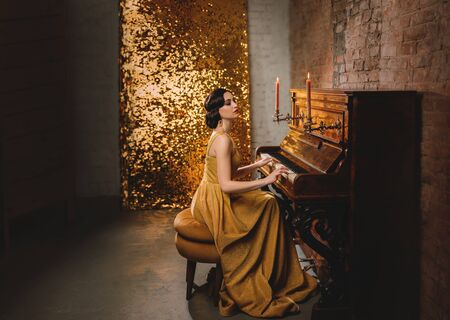 Young woman with finger wave hairstyle gold dress vogue fashion old style 1920 play piano candles romantic burning. Retro Great Gatsby backdrop shine sparkle room brick wall. Musician graduate party