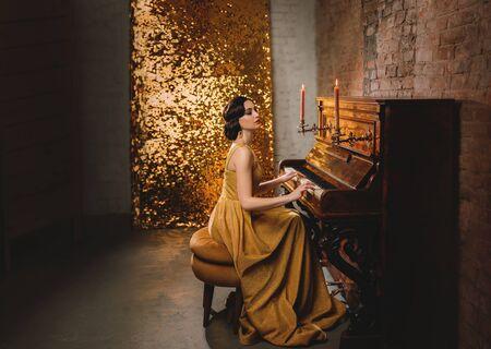 Mujer joven con peinado de onda de dedo vestido de oro moda moda estilo antiguo 1920 tocar piano velas quema romántica. Pared de ladrillo de la habitación del brillo del telón de fondo del gran Gatsby retro. Fiesta de graduados de músico