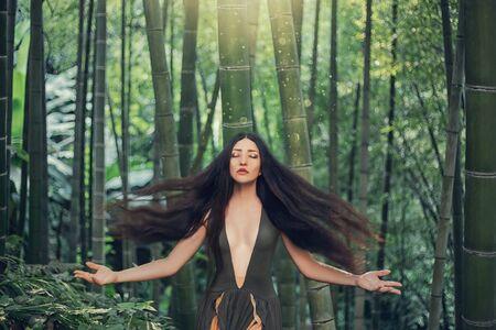 Fairytale tropicana wild sexy woman enjoy sunshine relax harmony reboot meditation. black long hair fly fluttering waving in wind. Backdrop green bamboo tropics Summer. spring magic art fantasy dress Foto de archivo