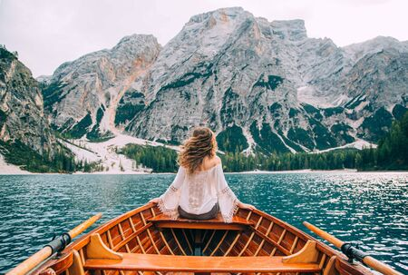 Silhouette woman with long hair flying fluttering wind, turned away sitting in boat. Tourist in white blouse long sleeves enjoy nature Italian mountains alpine lake. Backdrop river waves green forest