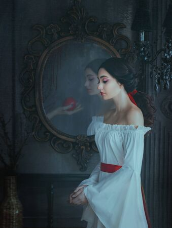 Portrait beautiful woman concept sleeping beauty fairytale Snow White. medieval clothes dress. Gothic princess makeup red lips. Ghost female hand with poison apple is reflected vintage antique mirror Banco de Imagens