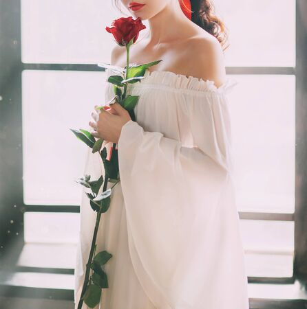 Mysterious silhouette young princess. White vintage dress. Red rose in hands