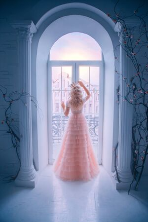 Sad princess looking window staying home. Queen lady enjoy evening sunset. concept freedom. long blonde hair. Pink vintage full dress white classic interior room. Silhouette woman turned away back
