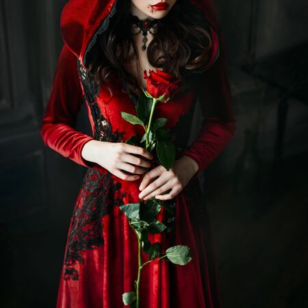 Portrait closeup silhouette gothic mystical vampire woman. Luxury long dress, hood. Vintage necklace. Medieval queen hold red rose in hands. black wavy hair. Festive halloween makeup, drops blood