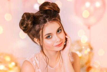 Portrait d'une fille aux cheveux roux, coiffure deux petits pains. Gros plan Main près du visage maquillage de soirée Princesse en robe rose pâle. Toile de fond de boules dorées brillantes, étincelles artistiques. fête de remise des diplômes d'anniversaire