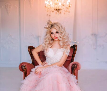 Charming beautiful delightful young girl princess sitting in antique vintage armchair waiting fairy miracle. Queen woman smiles mysteriously cute. Blonde long curly hair. Delicate pink airy dress Stock fotó