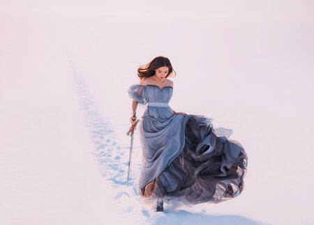 Fantasy lonely princess redhead hair elf walks winter frost white snow nature. Young beauty woman runs. queen holds hands magic blade sword. Blue silk long vintage dress fluttering fly wind in motion