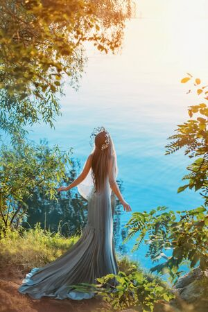 art fantasy photography. queen woman stands on river lake shore. sunset summer sun light. fashion model gray vintage long dress silhouette mermaid silver crown. concept divine freedom. Back rear view