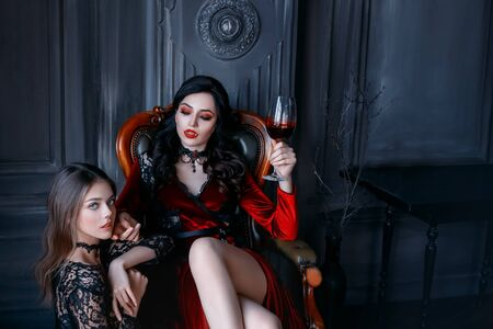 Sexy gothic woman vampire evil sitting on armchair holding glass of wine blood. bloody makeup sharp teeth fangs red lips. vintage medieval dress. frightened scared girl victim obeys at feet mistress