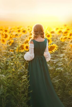 Young rural woman peasant back rear view. Bavarian beauty green dress vintage medieval national costume. Hairstyle blonde two braids. Girl walks in summer blooming field, yellow flowers sunflower