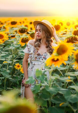 photo beauty woman model, blooming field. Rural fashion image. Yellow flowers sunflower. Blonde hair two braids, boater straw hat on head. Blurred backdrop bright sunny fantasy summer orange sunset