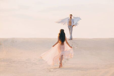Mysterious Silhouette Woman runs to her divine guardian angel man with white wings. fantasy pink vintage dress. brunette girl long hair fly in motion wind. Back rear view. Natural sand desert backdrop
