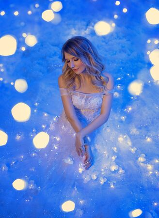 young beautiful woman fantasy queen. White luxury ball vintage fairy dress. Girl princess blond long hair Backdrop magic glow shiny sparkles stars, blue snow. luminous garland bright light on skirt