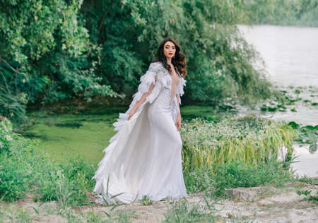 Beautiful Queen. charming woman bride walks on coast lake. Wedding outfit white long sexy dress, luxury cloak cape bird swan feathers. Brunette girl wavy loose hair. Backdrop summer nature green trees