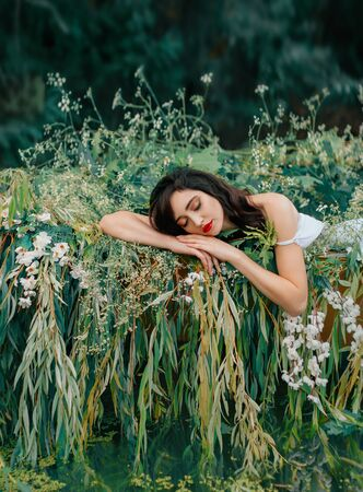 Young beauty sleeping woman resting in boat, decorated with willow branches, white flowers. Nymph girl closed eyes, enjoy silence summer nature river, water. Natural makeup red lips. Fantasy image 免版税图像