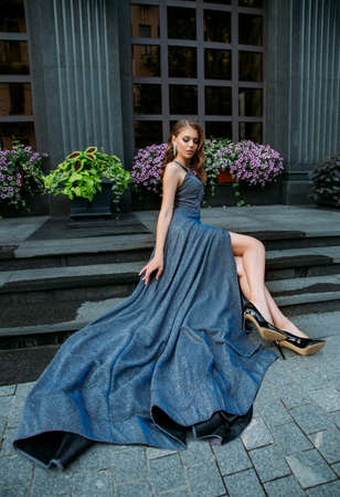 Beautiful young woman model sitting on steps modern city building, blooming petunia flowers. Chic luxurious long gray blue elegant party prom dress. Sexy bare legs black shoes. Stylish retro hairstyle