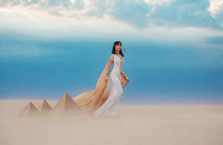 young beautiful woman model image Queen Cleopatra walks in desert Egyptian pyramids. Creative retro traditional gold jewelry bob hair cut. White satin long vintage dress, orange silk cape fly train 写真素材