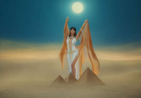 Artwork Fantasy egyptian beauty goddess Cleopatra raises hands to blue night sky, backdrop pyramid yellow sand dune bright moon light. Orange golden cape white sexy dress. Black hair queen Nefertiti