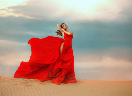 young sexy woman glamour queen stands. Beautiful desert, sand dune dramatic sky clouds. Red long silk elegant satin dress, slit up leg skirt, fluttering fly in wind motion. Girl fashion model posing