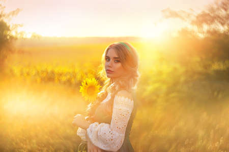 Artwork. Portrait young beautiful charming woman, national costume. Green sundress, white blouse. Blonde girl holding yellow sunflower in hands. Blurred backdrop bright summer nature sunny sunset