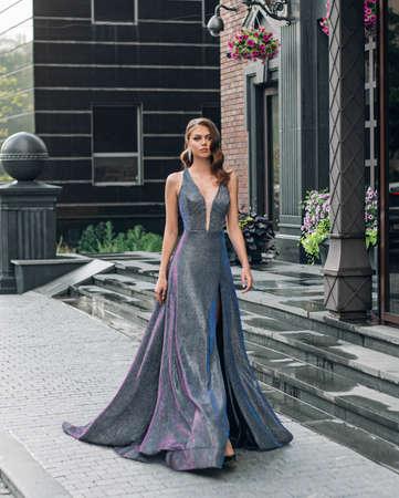 Beautiful young fashion gorgeous woman walks, modern black building, granite steps. Brunette girl hairstyle Hollywood wave retro style. Long evening gray luxury glamor iridescent shiny elegant dress