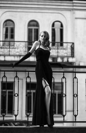 Sexy girl in classic evening dress. Black and white photo film. Luxury vintage woman. Beautiful Lady in retro image. Glamour queen Hollywood wave hair. Noir fashion model posing on balcony of Venice