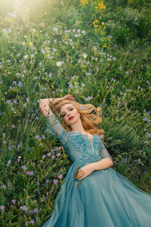 Young beautiful woman lying on green flowering grass. Purple yellow flowers. Blue luxury evening vintage tulle dress. Girl princess enjoys summer nature. Blonde long wavy hair red lips romantic face 写真素材