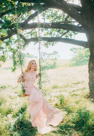 beautiful woman nymph sitting on magic swing. Long beige peach silk vintage fashion dress. Bride Princess blonde hair. Fine art wedding photo. Autumn foggy backdrop nature green grass summer trees