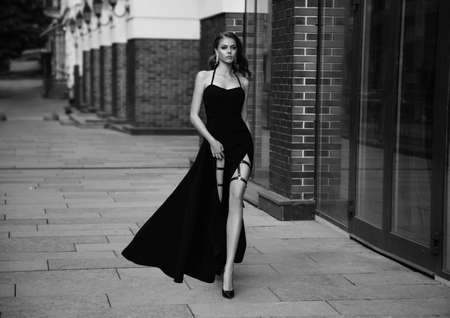 Film grain added. Sexy girl in classic evening trendy dress. Black and white photo. Luxury vintage woman with long leg. Beautiful retro Lady. Glamour queen. Noir fashion model walks down old street