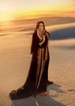 Beautiful mysterious arab woman in black muslim abaya dress. head is twisted with silk handkerchief chain hides face. Fantasy Girl walks in desert, art background sand golden sunset. Queen Concubine Stockfoto