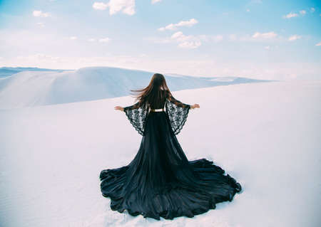 Rear view Silhouette of Beauty woman. Queen in black clothes stands in desert. Girl fashion model. long, silk dress with train. Back of luxury glamorous elegant goddess. background white sand blue sky