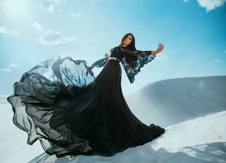 Beautiful mysterious Arab woman queen in black clothes. Girl fashion model posing, dancing in long, silk dress, fabric flies in wind motion. Princess walks in desert, background white sand blue sky Stockfoto