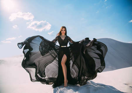 Beautiful sexy woman queen in black clothes. Girl fashion model. long silk dress fabric flies in wind, luxury glamorous elegant goddess shows bare legs in cut of skirt. background white sand blue sky Stockfoto