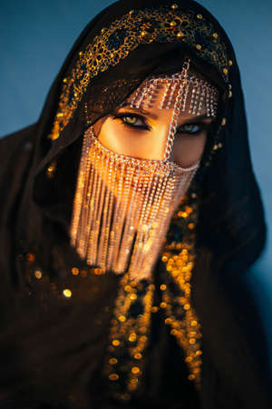 portrait of young beautiful oriental mysterious girl. The woman looks into the camera. The face is hidden by a golden veil. Luxurious evening make-up, smoky eyes. The head is covered with black scarf Standard-Bild