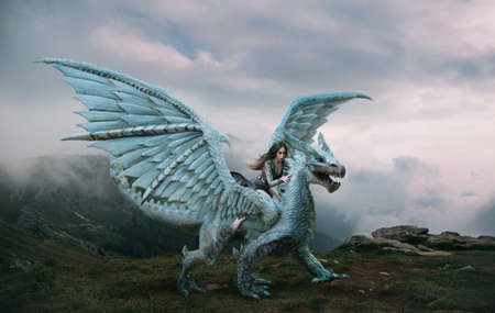 A young woman sits astride a dragon. Fantasy photography. A huge creature with spikes and wings stands on top of a mountain. Beautiful nature sky and white clouds. Stock Photo