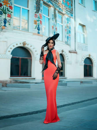 Elegant retro lady in a long red evening glamour dress. Young stylish trendy woman in a black hat with wide brim and high tulle gloves. bow at the neck. Adult woman fashion model stands on the street Banco de Imagens