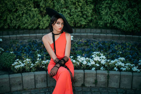 Elegant retro lady in a long red evening dress. Young stylish woman in a black hat with wide brim and high tulle gloves. Adult woman fashion model sitting near a blooming flower bed in the garden Banco de Imagens