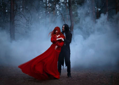 Blurred silhouette of a Gothic couple dancing in the fog. A vampire man in black tailcoat with long hair embraces seduces a woman in a long red medieval dress. The fabric and hair are flying in wind