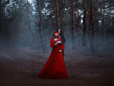 Gothic couple standing in the fog. A vampire man in a black tailcoat with long hair embraces a woman in a long red medieval dress. Fantasy art photo. Background deep dark forest, trees, blue fog.