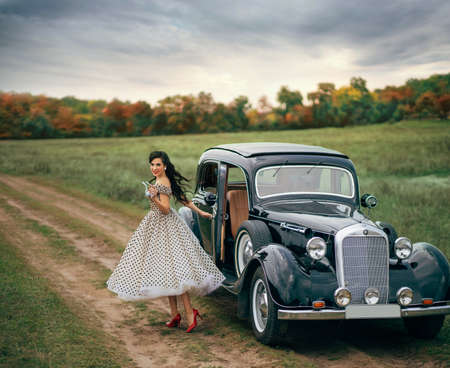 Young beautiful happy retro woman near the old car. Attractive elegant lady in vintage white polka black dot retro dress. Pin-up hairstyle. Cheerful girl standing on road. Autumn nature, yellow trees Stock Photo