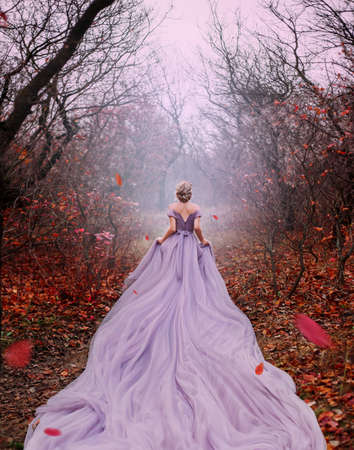 Art fantasy beautiful woman queen walk in autumn mystic forest, orange leaves trees. Magic light divine glowing in gothic fog. Girl lady princess. Medieval purple dress long train. back rear view