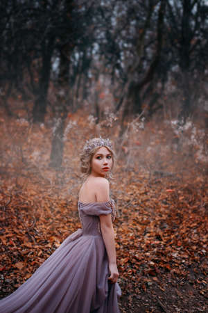 Art bright photo, fantasy beautiful woman queen walk in autumn mystic forest. Orange falling leaves black trees. Magic gothic fog. Romantic Girl lady princess in medieval purple long dress, crown