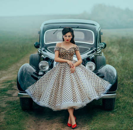 Young beautiful woman in pin-up style clothes posing near black retro car. Polka dot white dress, vintage hairstyle, red high heels. Background road green nature fog. Girl fashion model driver